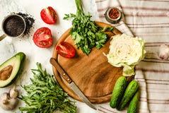 Greens, tomaten, komkommers, kruiden, avocado's, groenten, springen vers voedsel op Het voorbereiden van ruwe salade Houten raad, stock foto's