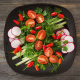 Greens and vegetable salad on a black plate in style  rustic Stock Photography