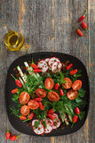 Greens and vegetables salad on a black plate  old wooden boards Stock Image