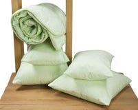 Greens verdraaide die deken en hoofdkussens op een plank op witte achtergrond wordt geïsoleerd Stock Foto