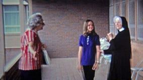 GREENSBORO, NC -1971: Katholieke non die jong meisje zegenen alvorens zij weg reist stock videobeelden