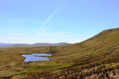 Greensett Moss on Whernside, Ingleborough at rear. Looking south across the eastern slopes of Whernside past a small tarn on Greensett Moss to Ingleborough with Royalty Free Stock Image
