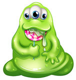A greenslime baby monster eating a lollipop Stock Image