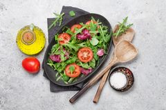 Greent salad mix. Green salad mix plate with tomatoes, rucola, frisee, radicchio and lamb`s lettuce. Olive oil and spices. Top view stock images