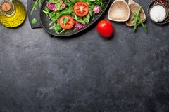 Greent salad mix. Green salad mix plate with tomatoes, rucola, frisee, radicchio and lamb`s lettuce. Olive oil and spices. Top view with copy space royalty free stock photography