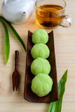 Greentea mochi flavored with bean filling and cup of tea on wood Stock Image
