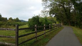 Greenway walk near Marion NC with weathered wooden fence. And green fields to one side, mature green trees to the other stock photos