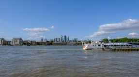 Greenwich Pier with river cruiser waiting to depart. Greenwich, London, Uk - August, 10 2018, Greenwich pier with a river cruiser moored and view of Canary royalty free stock image