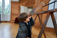 Greenwich, London, UK - October 30 2016: A young boy looks through an antique telescope.  royalty free stock photography
