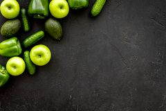 Greeny cocktail ingredients. Fitness smoothie. Cucumber, pepper, apple on black background top view space for text.  Royalty Free Stock Photo