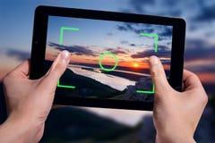 Greep zwarte tablet op handen Het schieten van aardlandschap Stock Afbeelding