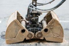 Greepemmer van een graver die op de weg liggen Stock Afbeelding