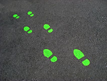 Green Footprints. Set of green footprints on asphalt. Could beused to symbolize environmental stewardship Royalty Free Stock Photography