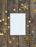 greeteng卡片的嘲笑在与圣诞节装饰闪烁雪花和金子的木土气背景担任主角五彩纸屑 邀请, 库存照片