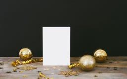 greeteng卡片的嘲笑在与圣诞节装饰闪烁雪花,中看不中用的物品,响铃,蛇纹石的木土气黑暗的背景和 免版税库存图片