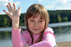 Greeting. The little girl in a pink jacket waves a hand Royalty Free Stock Photos