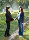 Greeting. Two young beautiful women against park Stock Image