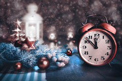 Greeting card with alarm clock showing five to twelve and winter arrangement. Stock Images