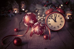 Greeting card with alarm clock showing five to twelve and winter Royalty Free Stock Image