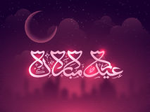 Greeting Card with Arabic Text for Eid celebration. Glowing Arabic Islamic Calligraphy of text Eid Mubarak on Mosque silhouetted cloudy night background Stock Image