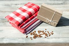Greeting card. Birthday gift box with stack of tableclothes and. Roasted coffee beans on rustic bright wooden table. Outdoor. Card concept Stock Images