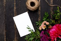 Greeting card with a bouquet of flowers on a dark vintage wooden background royalty free stock image
