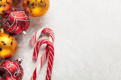 Greeting card with Christmas decorations in red and gold balls, snow and candy canes on a white concrete background. Top. View with copy space. Overhead stock photos