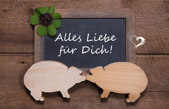 Greeting card with clover and two wooden pigs - like a couple - Stock Image