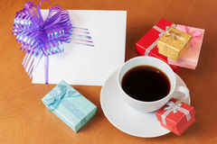 Greeting card , colored gift boxes  and white coffee cup Royalty Free Stock Images