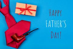 Greeting card with composition of red neck tie, gift box and smoking tobacco pipe with inscription Happy Father`s day. Greeting card with composition of mans royalty free stock photography