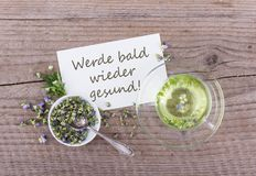 Get well soon. Greeting card with a cup of tea with dried and fresh Viola and white card with german text: get well soon royalty free stock photo