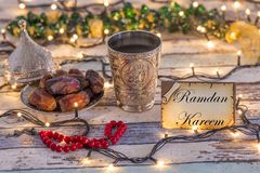 Greeting card  with dates, rosary, and metal water cup with Allah text in arabic. Greeting card Ramadan Kareem with dates, rosary, and metal water cup with Allah royalty free stock photo