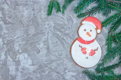 Greeting card with decorative gingerbread, spruce branch and gift boxes on a gray cement background. Overhead of christmas new yea