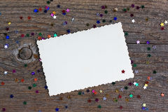 Greeting card: empty paper form with stars confetti on wooden background Royalty Free Stock Images