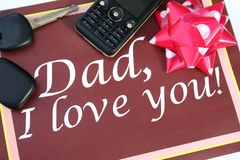 Greeting card for father. Brown greeting card for father with mobile phone, car key and ribbon Royalty Free Stock Photo