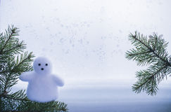 Greeting card with fir branches and a snowman. On the background of window frost Royalty Free Stock Photography