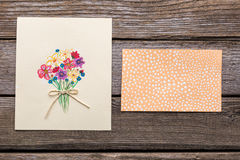 Greeting card with flowers on wooden background. Stock Photos