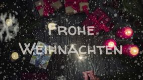 Greeting card Frohe Weihnachten, Merry Christmas in german language. Falling snow, candles and gifts stock photography