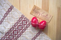 Greeting card Happy Easter! Easter Eggs. Pink bow wrapped eggs on the grey background with tablecloth. Rustic style. The concept of stylish decoration for royalty free stock photography