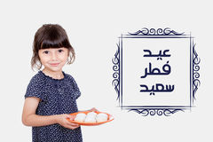 Greeting Card : Happy Eid. Happy kid celebrating Eid El Fitr - Muslim girl presenting kahk ( cookies ) in the feast Stock Photos