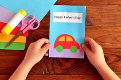 Greeting card Happy father's day. Child holds a card in his hand. Greeting card Happy father's day. Paper sheets, scissors, glue. How to make a greeting card Royalty Free Stock Photography