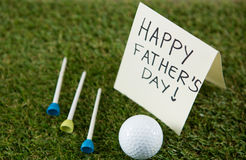 Greeting card with happy fathers day text by golf ball and tees on field. Close up of greeting card with happy fathers day text by golf ball and tees on grassy Stock Images