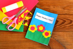 Greeting card Happy mother's day - children crafts. Scissors, glue, paper scraps, paper sheets on brown wooden background Stock Images