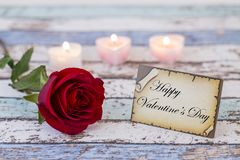 Greeting card with Happy Valentine`s Day text, single red rose, and candle lights. Background stock image
