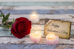 Greeting card with Happy Valentine`s Day text, single red rose, and candle lights. Darker stock photo