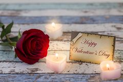 Greeting card with Happy Valentine`s Day text, single red rose, and candle lights. Darker stock images