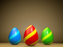 Greeting card illustrating three easter eggs. Greeting card illustrating three colored easter eggs.Copy space on top for own text and wishes.Brown background Royalty Free Stock Photo