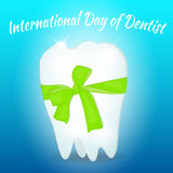 Greeting card for International Day of Dentist . White tooth with green bow.  Royalty Free Stock Images