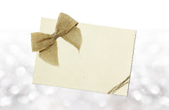 Greeting card with jute ribbon bow. On blurred lights Royalty Free Stock Image