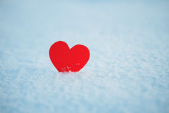 Greeting card with  lonely heart on the dazzling blue snow Royalty Free Stock Images